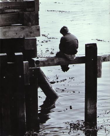 Solitary Young man on pilings of pier Monterey California 1970 &copy all rights reserved.